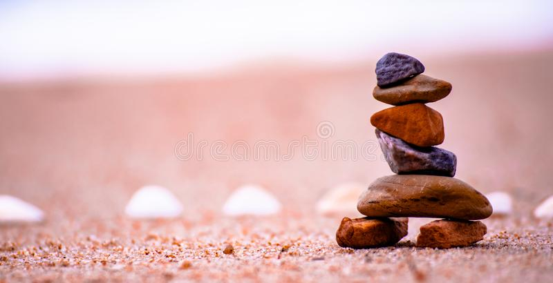 Small stone on the sea beach. Look like a robot on the sand beach. Arrangement of Small stone on the sea beach and blurry background in the morning holiday stock photo