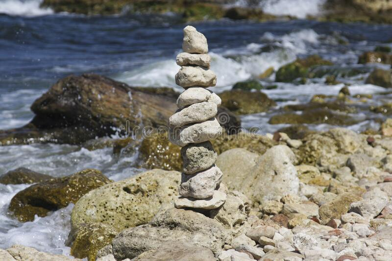 Arrangement of stones on the seashore. Sunny day. Storm. The waves. Balance.  stock images