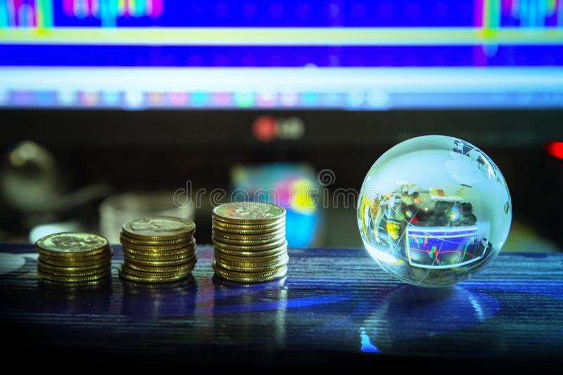 Arrangement of World globe crystal glass and coin at office table on charts stock data on computer screen background. Global royalty free stock image