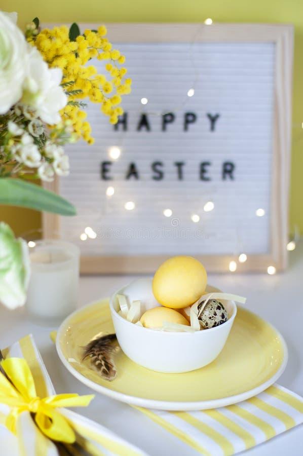 Arrangements de table de Pâques avec les oeufs et les fleurs peints de ressort photos stock