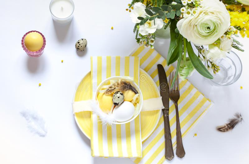 Arrangements de table de Pâques avec les oeufs et les fleurs peints de ressort photo libre de droits