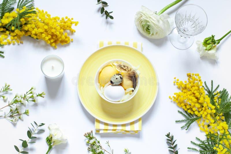Arrangements de table de Pâques avec les oeufs et les fleurs peints de ressort photo stock