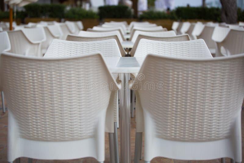 Arrangera i rak linje stolar och tabeller arkivfoto