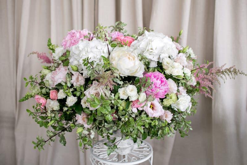 Arrangez les fleurs dans un vase romain blanc photo stock