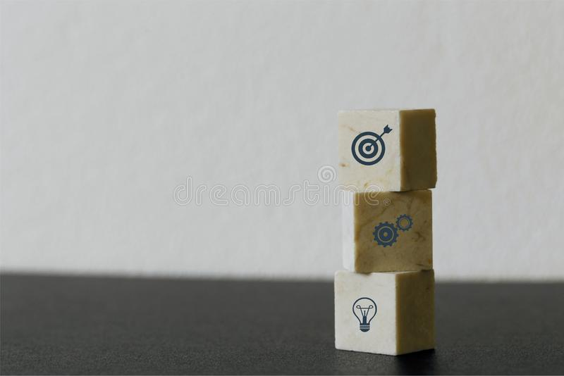 Arranging Marble cube block stacking with icon business strategy and action plan on wood background. Minimal concept.  royalty free stock photos