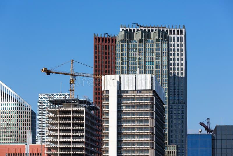 Arranha-céus com construção de um prédio de escritórios novo fotos de stock royalty free
