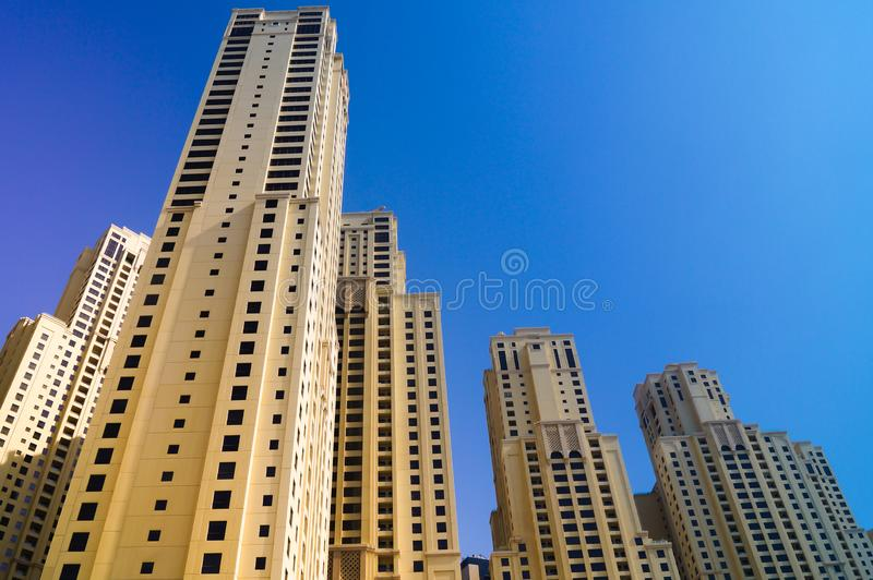 Arranha-céus de baixo em Dubai contra o céu azul imagem de stock