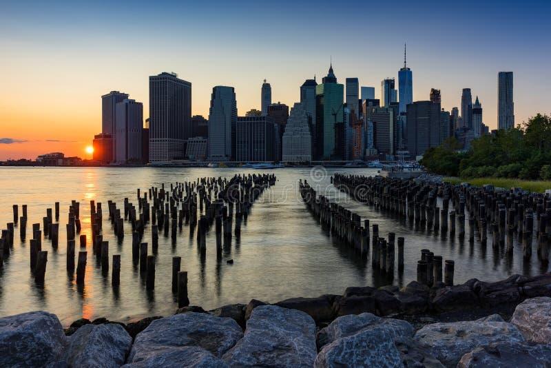 Arranha-céus do Lower Manhattan e das pilhas de madeira no por do sol Manhattan, New York City fotografia de stock