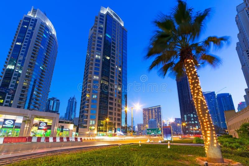 Arranha-céus iluminados do porto de Dubai na noite fotos de stock