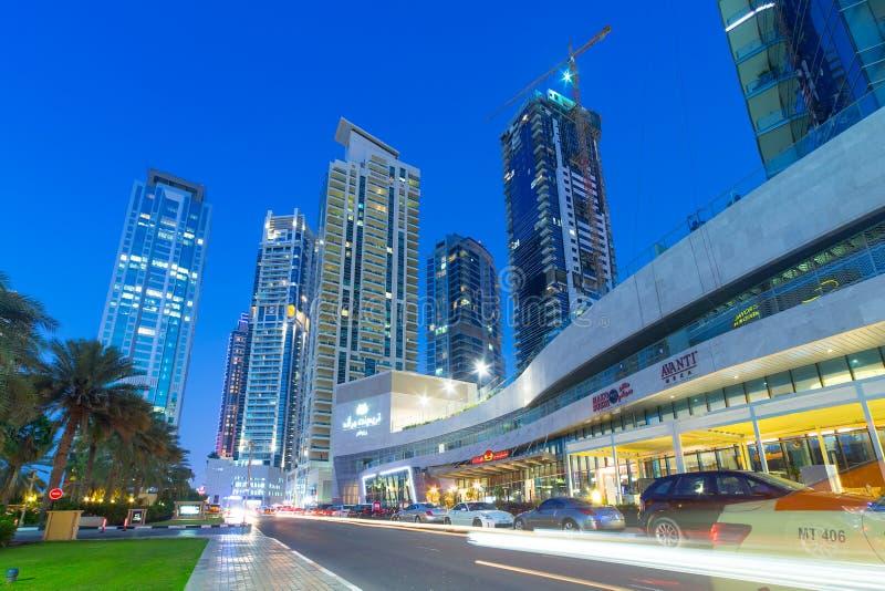 Arranha-céus iluminados do porto de Dubai na noite imagens de stock royalty free