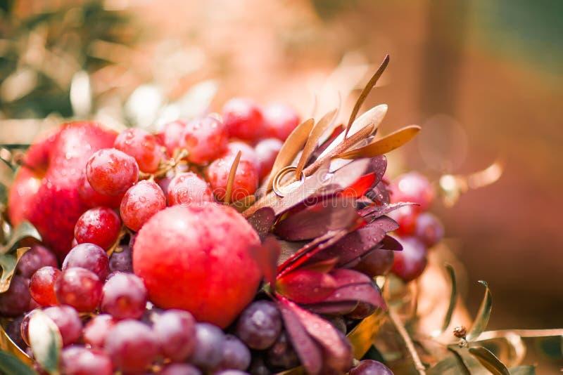 Arranjo bonito dos frutos, das flores e das alianças de casamento fotos de stock royalty free