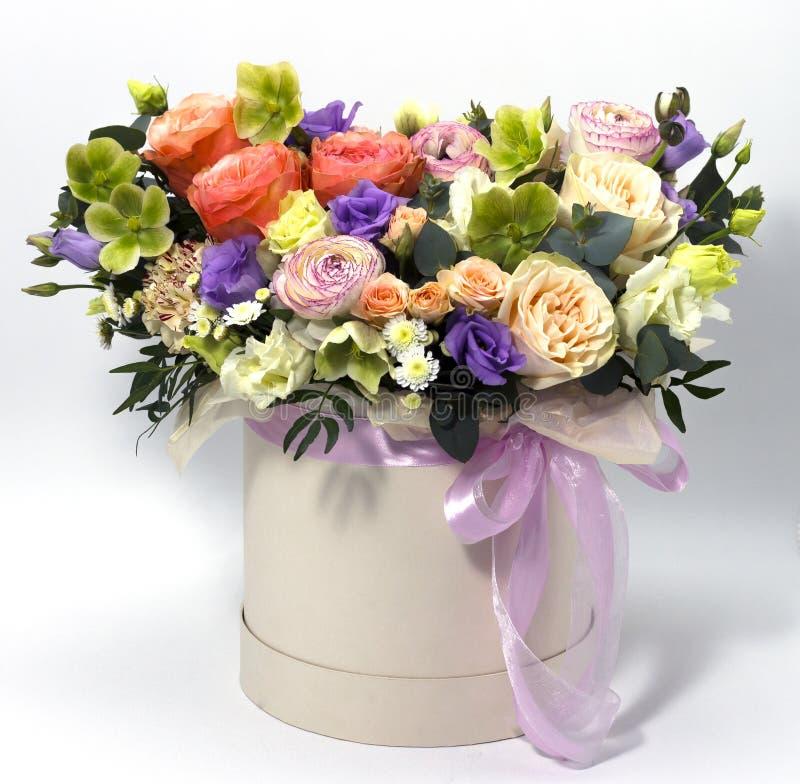 Arranjo de flor bonito em uma caixa do chapéu em um fundo floral do fundo branco fotos de stock royalty free