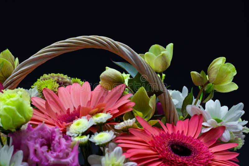 Arranjo de flor brilhante em uma cesta branca em flores escuras de um fundo em uma cesta de vime foto de stock