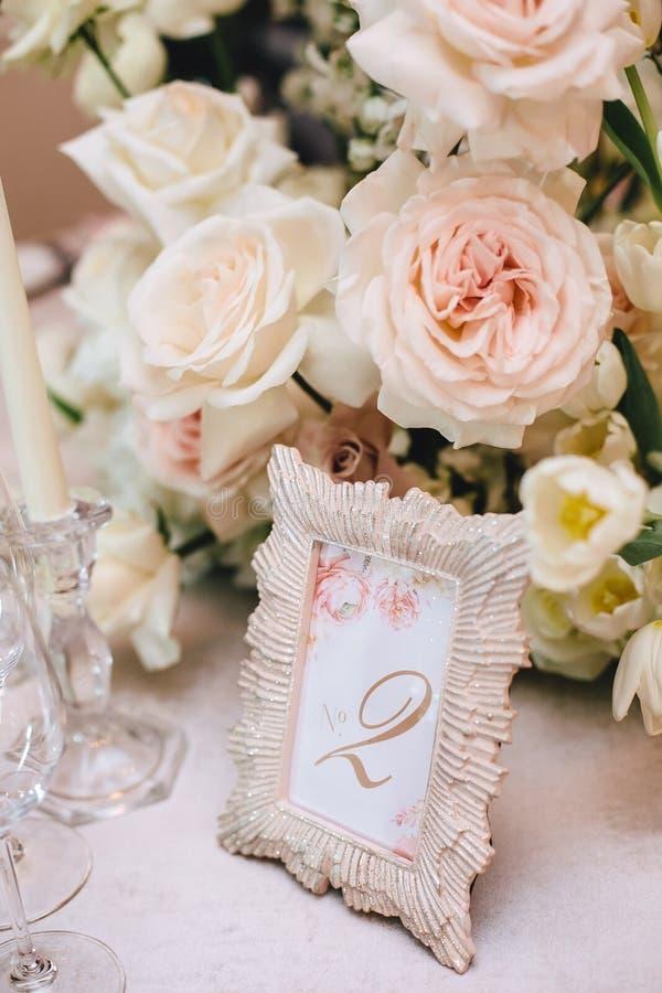 Arranjo de flor das rosas brancas e um quadro bonito com o número dois, a numeração da tabela no banquete fotos de stock