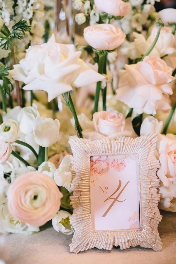 Arranjo de flor das rosas brancas e um quadro bonito com o número quatro, a numeração da tabela no banquete foto de stock