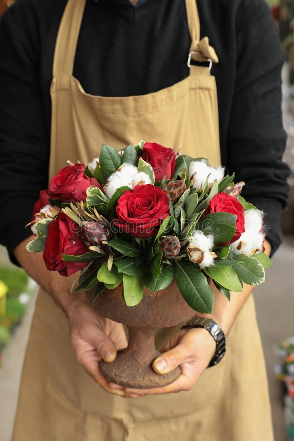 Arranjo de flor festivo de rosas vermelhas e de flores do algodão no florista do vaso que guarda no boutique das flores fotos de stock royalty free