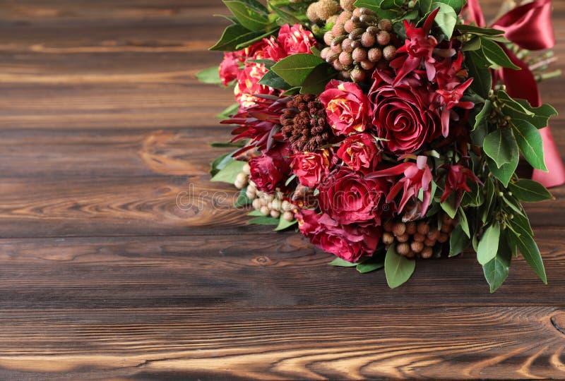 Arranjo de flor fresca bonito de rosas vermelhas no fundo de madeira imagem de stock