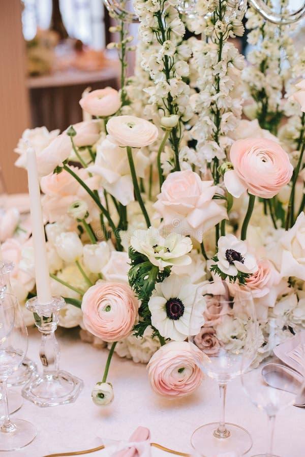 Arranjo de flor luxuoso dos botões de ouro, das rosas brancas em uma tabela de banquete, junto com castiçal e vidros para o vinho foto de stock royalty free