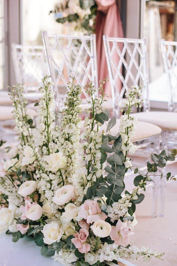 Arranjo de flor de rosas cor-de-rosa, botões de ouro e sinos e eucalipto brancos perto das cadeiras transparentes fotos de stock
