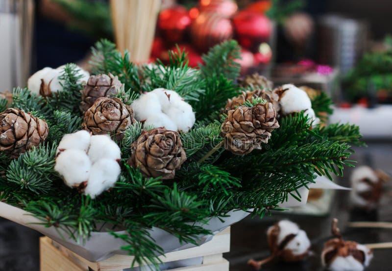 Arranjo do inverno de cones, de ramos e de algodão de abeto na caixa de madeira imagens de stock