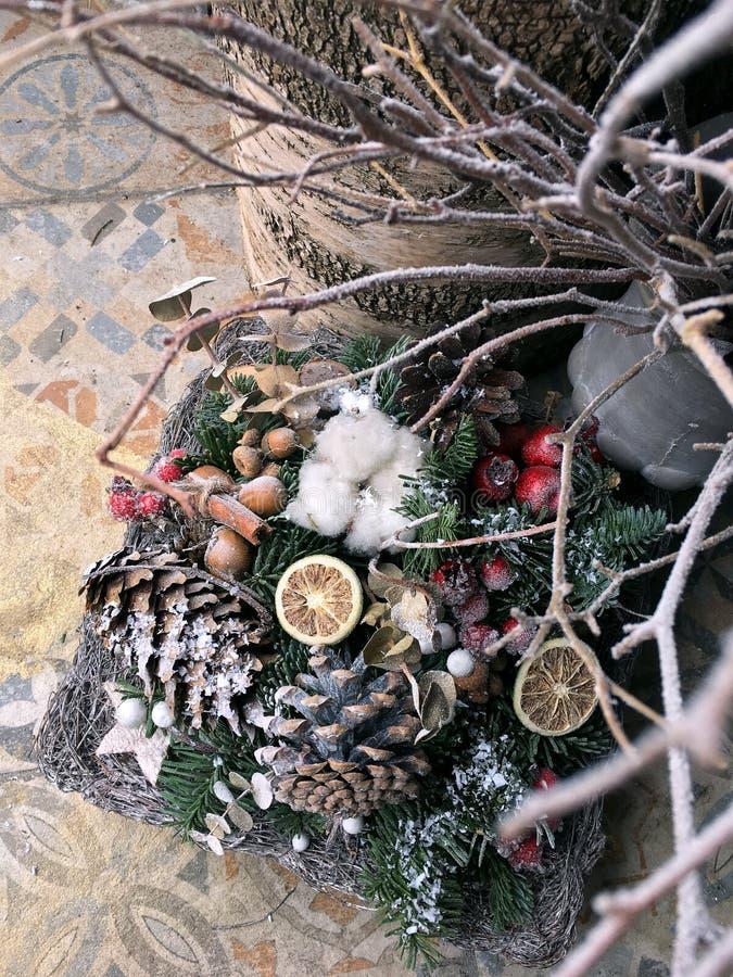 Arranjo do inverno de cones, de ramos e de algodão de abeto no lugar de funcionamento do ` s do florista Ano novo, ramalhete do N imagem de stock