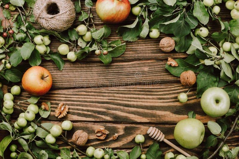 Arranjo flatlay acolhedor do quadro do outono com ramos de árvore da maçã, frutos maduros, colher, nozes e guita em de madeira imagem de stock