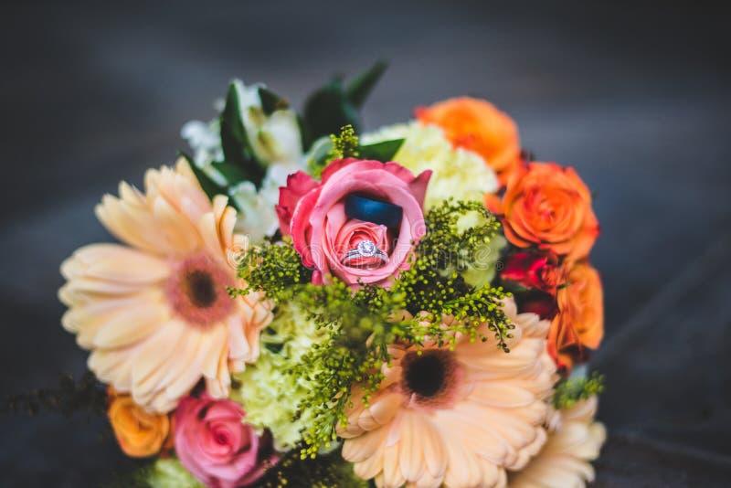 Arranjo floral com alianças de casamento fotos de stock