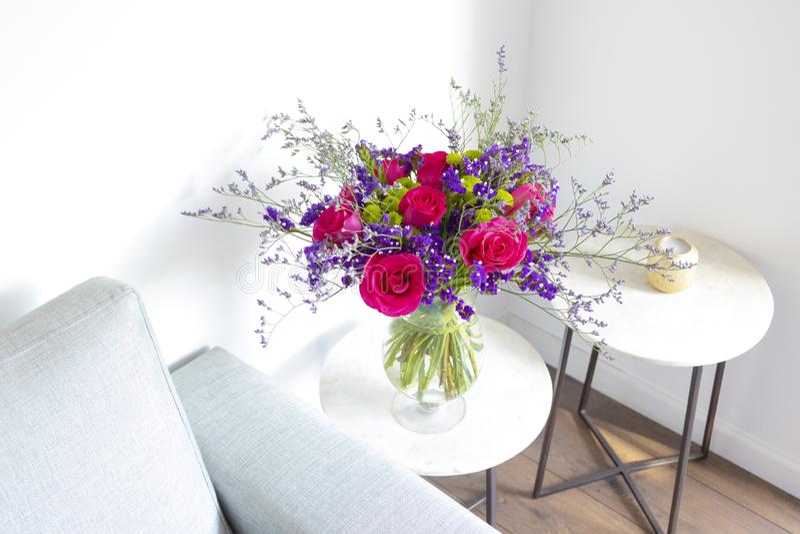 Arranjo floral das rosas e dos limoniums que decoram a sala de visitas fotografia de stock