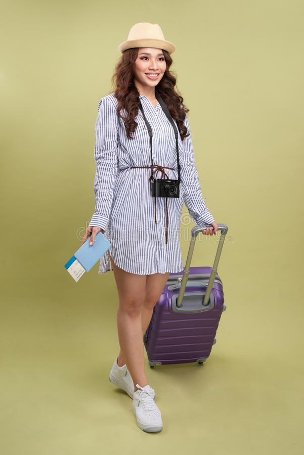Arrasto asi?tico emocionante da mulher uma bagagem, retrato completo do comprimento isolado no fundo branco fotografia de stock