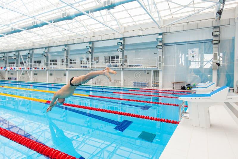 Arrastre de la natación del nadador del hombre en agua azul fotos de archivo