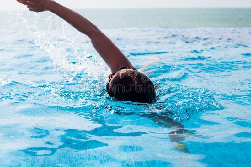 Arrastre de la natación de la mujer joven en una piscina con vista al mar imagen de archivo libre de regalías