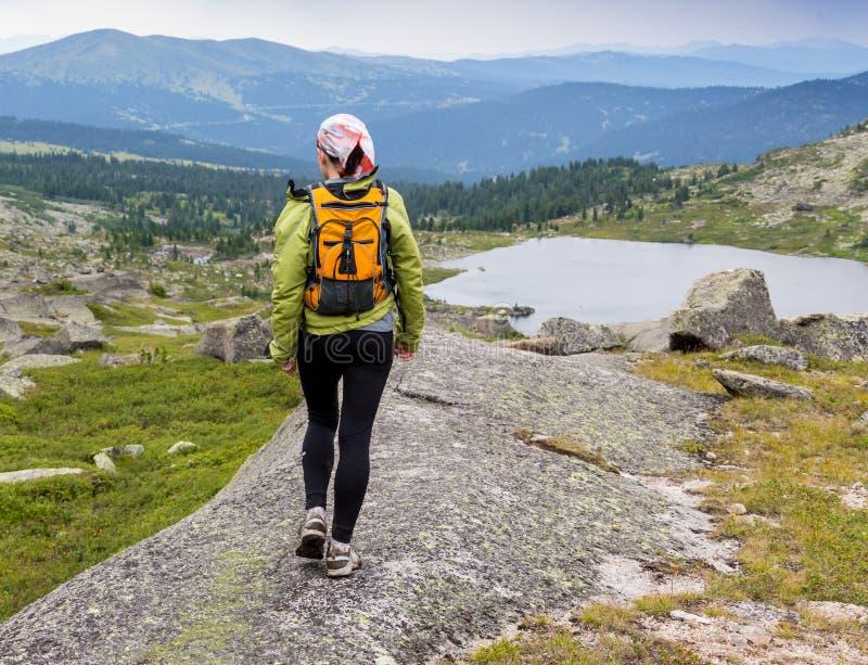 Arrastre el campo a través corriente de la mujer en montañas en día hermoso del verano fotografía de archivo