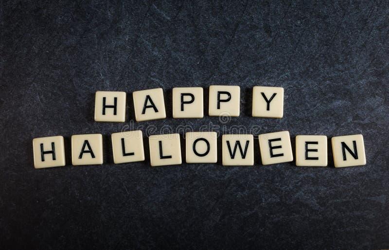 Arrastrese las tejas de la letra en feliz Halloween negro del deletreo del fondo de la pizarra fotos de archivo libres de regalías