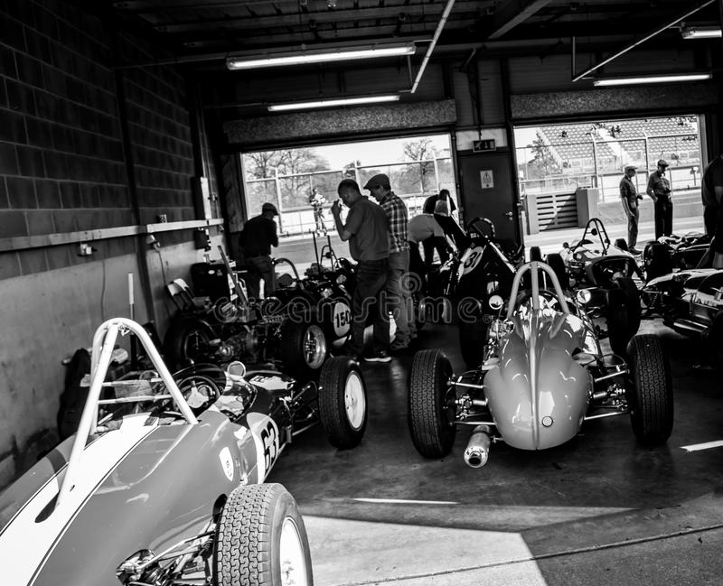 An array of historic racing cars being prepared for a race. stock photos