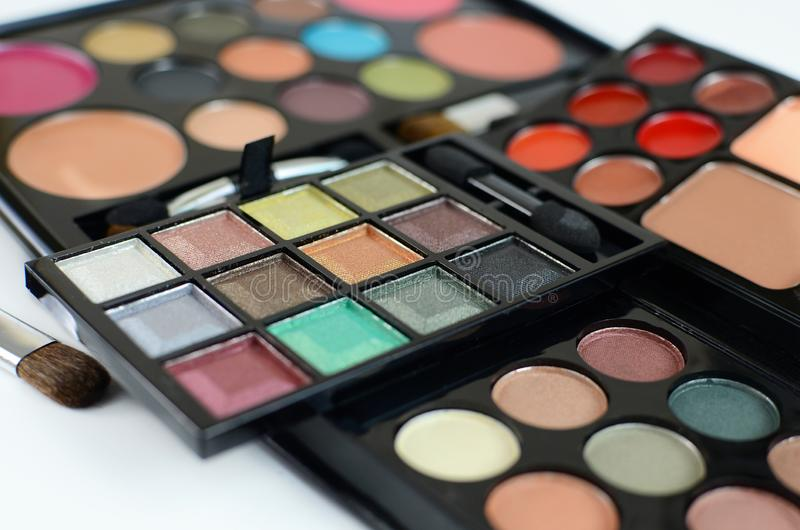 An array of makeup or cosmetics. Shallow depth of field puts emphasis on different colored eye shadows. stock photo