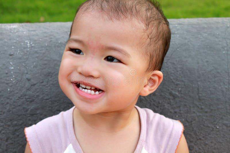 Arreganho asiático do bebê, fazendo uma face fotografia de stock