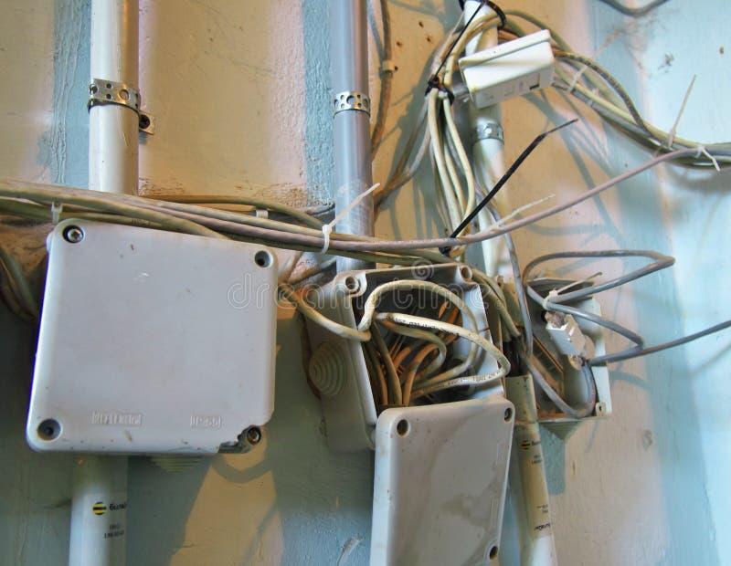Arreglado aleatoriamente en los alambres de la red de comunicaciones en cajas en la pared foto de archivo libre de regalías