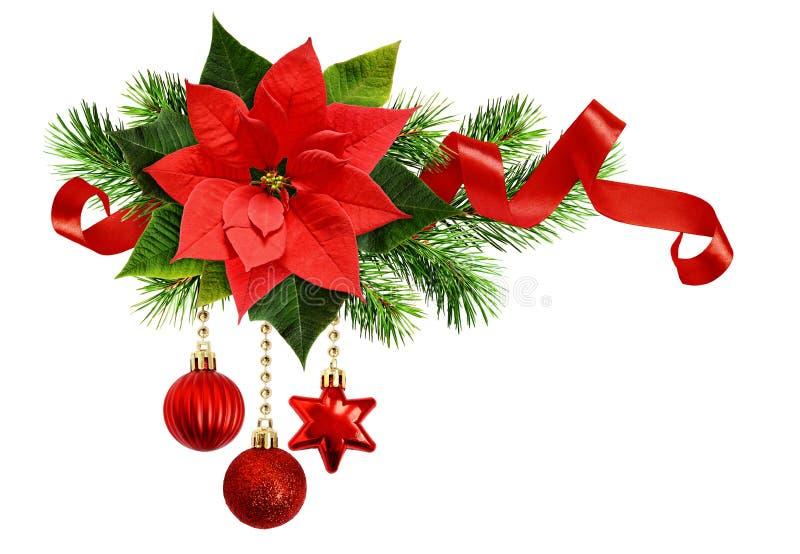 Arreglo con la flor de la poinsetia, ramitas del pino, decoros de la Navidad fotografía de archivo