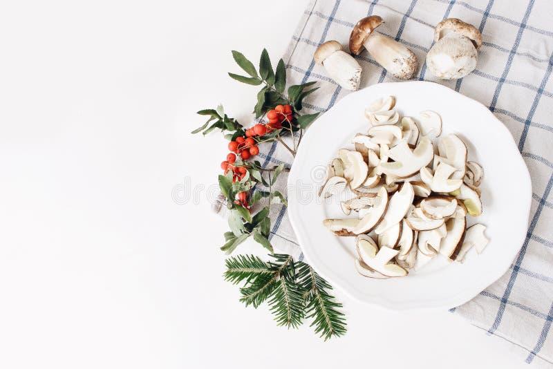 Arreglo de la comida del otoño Composición de las setas enteras y cortadas del porcino, ceps en la placa Bayas de serbal, hojas,  fotografía de archivo