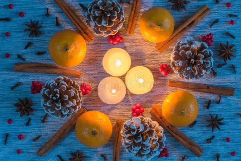 Arreglo de la Navidad de las velas rodeadas por la guirnalda de los pinecones, naranjas, palillos de canela fotos de archivo