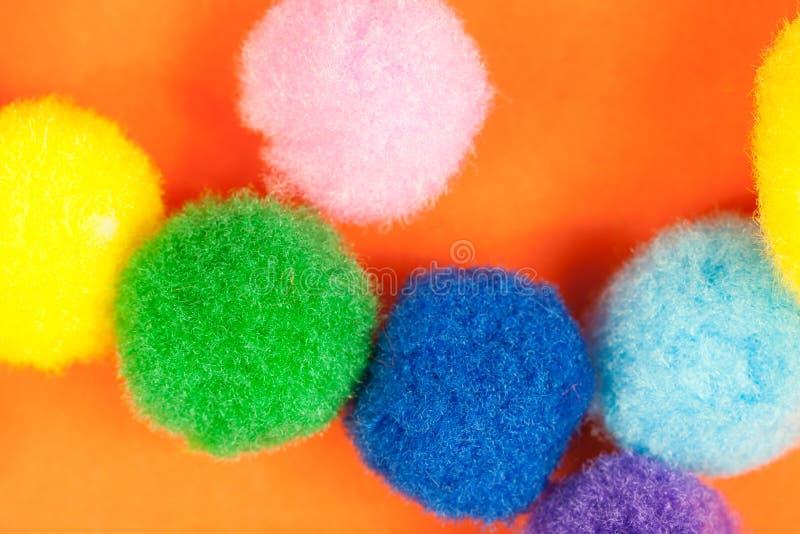 Arreglo de las bolas suaves de la materia textil borrosa mullida colorida viva en fondo de papel anaranjado vibrante imagen de archivo libre de regalías