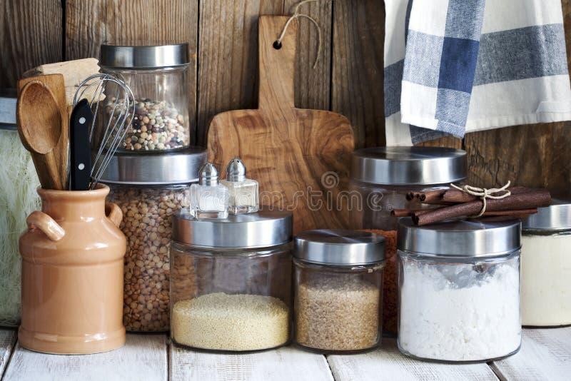 Arreglo de los productos alimenticios y de los utensilios secos de la cocina foto de archivo