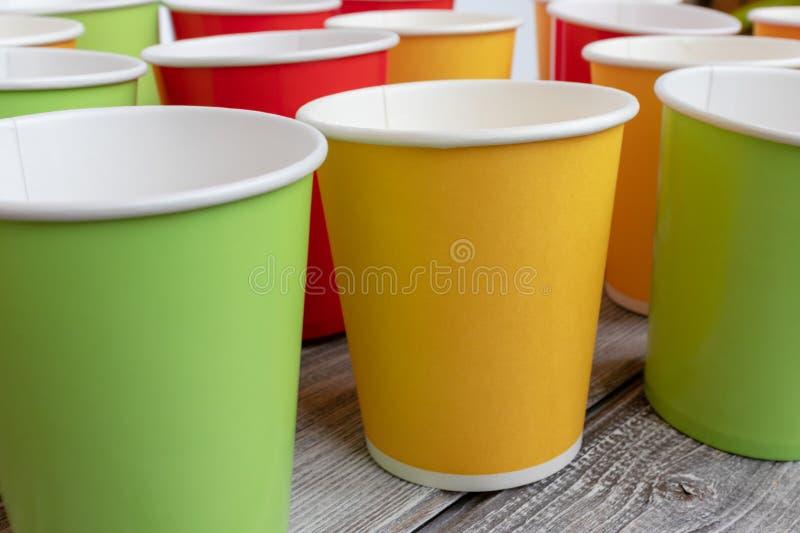 Arreglo de reciclar las tazas de papel coloridas disponibles, vidrio de color rojo, amarillo y verde imagen de archivo