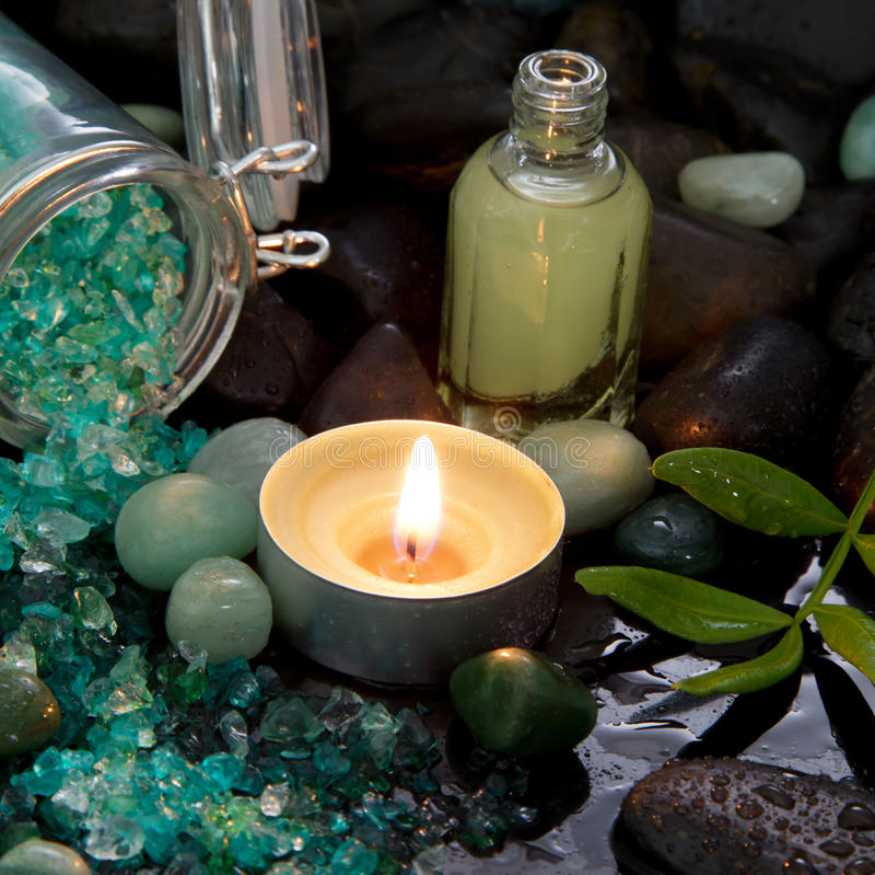 Arreglo del balneario - aceite natural del masaje con una vela ardiente imagen de archivo