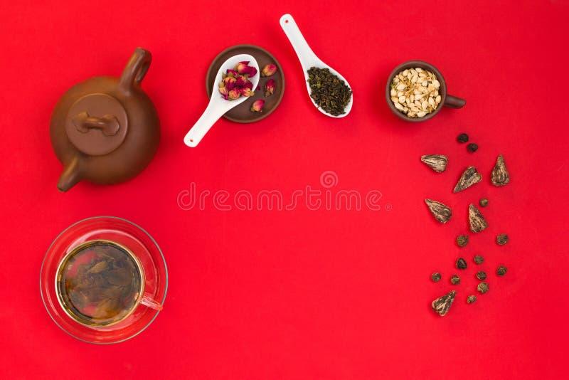 Arreglo del marco de Flatlay con las hojas de té verdes chinas, los brotes color de rosa, las flores del jazmín y un pote del té  fotos de archivo