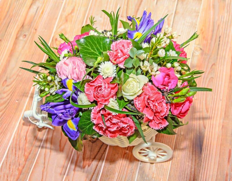 Arreglo floral con la bicicleta blanca y las rosas coloreadas de las flores, foto de archivo