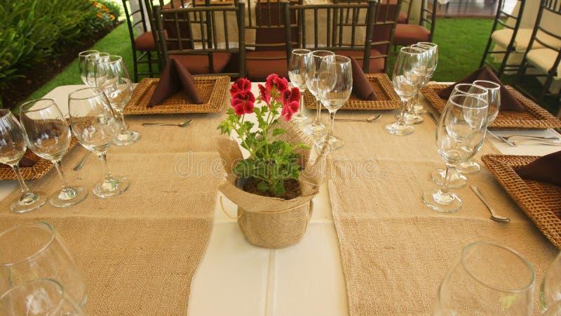 Arreglo floral en un pote con el abrigo rústico del paño en una tabla dispuesta y adornada para un almuerzo en el jardín de una c foto de archivo libre de regalías