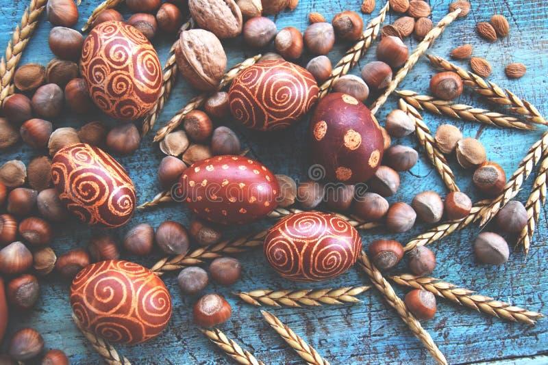 Arreglo natural de los huevos de Pascua con las avellanas, deletreadas, huesos de albaricoque nueces imágenes de archivo libres de regalías
