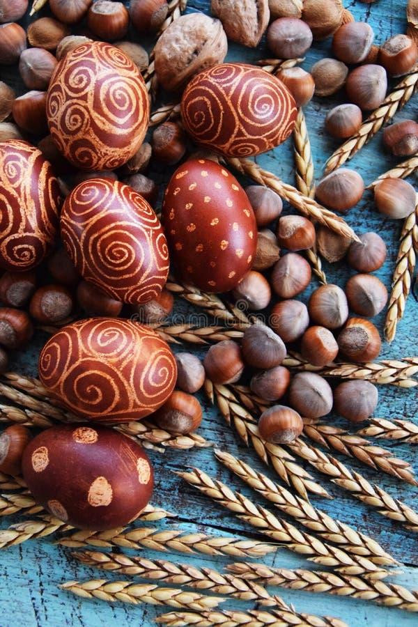Arreglo natural de los huevos de Pascua con las avellanas, deletreadas, huesos de albaricoque nueces fotos de archivo