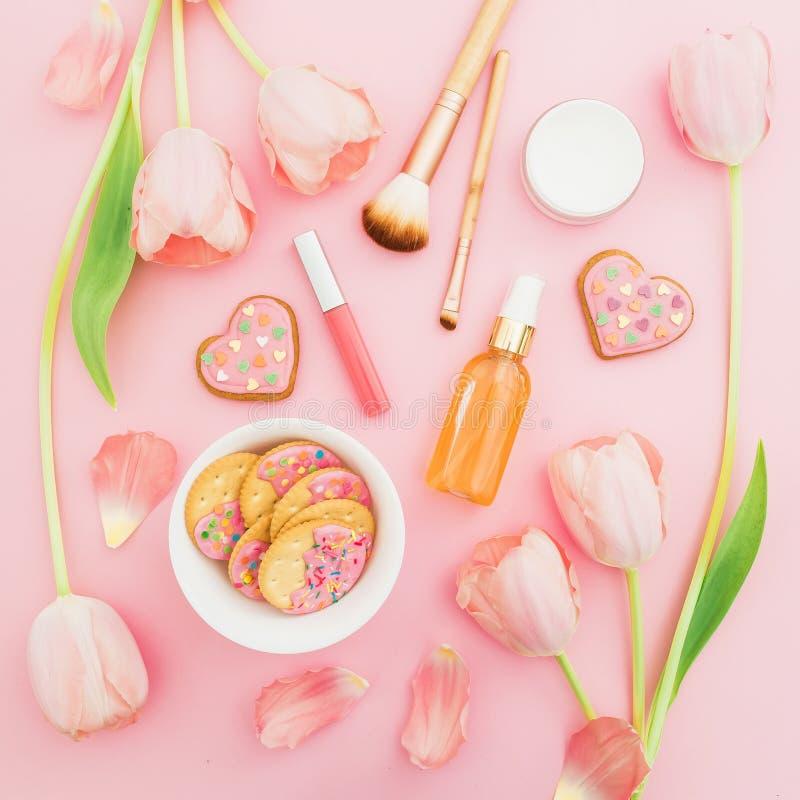 Arreglo rosado de las flores, de los cosméticos y de las galletas en fondo en colores pastel rosado Endecha plana, visión superio fotografía de archivo